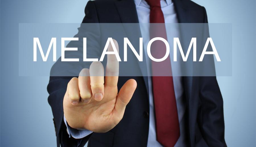 Мужчина в пиджаке пишет слово меланома пальцем